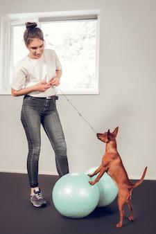Mulher e cachorro. mulher de cabelos escuros vestindo jeans e camiseta branca brincando com um cachorro fofo