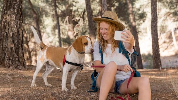 Mulher e cachorro se divertindo e tirando uma selfie