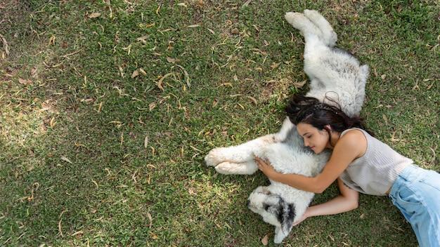 Mulher e cachorro sentados na grama