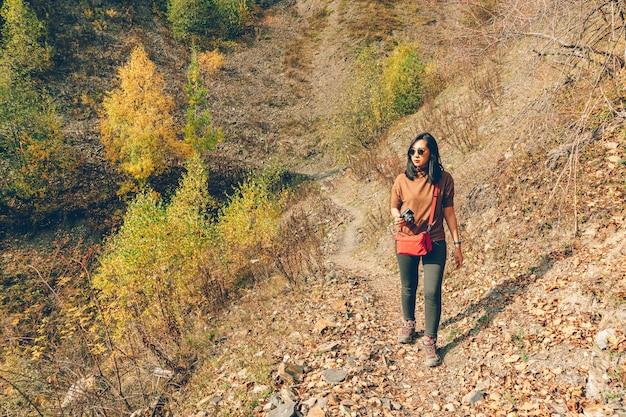 Mulher é caminhadas na colina com árvores amarelas e verdes.