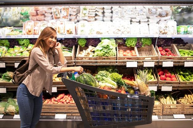 Mulher e carrinho de compras no supermercado