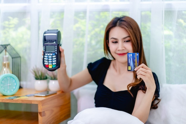 Mulher e cartão de crédito com uma máquina de furto de cartão de crédito na cama, o conceito de administrar um negócio on-line o tempo todo