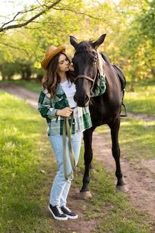 Mulher e cavalo em tiro completo