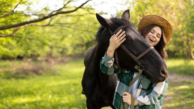 Mulher e cavalo felizes em tiro médio