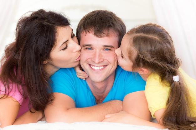 Mulher e criança beijando seu pai. família feliz se divertindo em casa