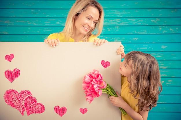 Mulher e criança com buquê de flores sobre fundo verde. conceito de férias em família de primavera. dia das mães