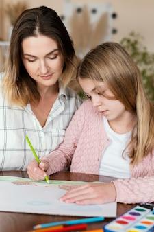 Mulher e criança desenhando juntos em close-up