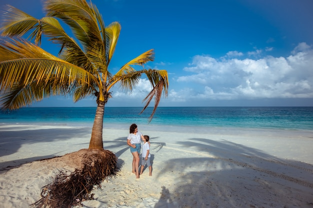 Mulher e criança em pé debaixo de uma palmeira no oceano