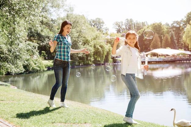 Mulher e criança estão brincando juntos. menina está soprando bolhas de sabão. mulher está andando atrás dela e sorrindo. eles estão passando um bom tempo juntos.