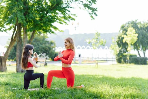 Mulher e criança fazem ioga no parque verão, sol, mãe e filha, saúde, esportes ao ar livre