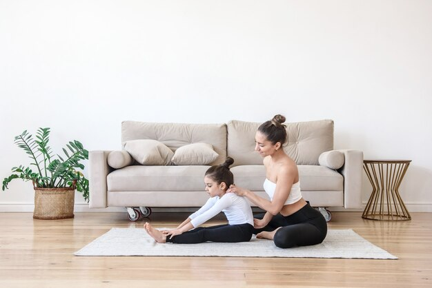 Mulher e criança menina estão envolvidas em alongamento de ioga em casa no chão da sala de estar. mãe e filho praticam esportes juntos