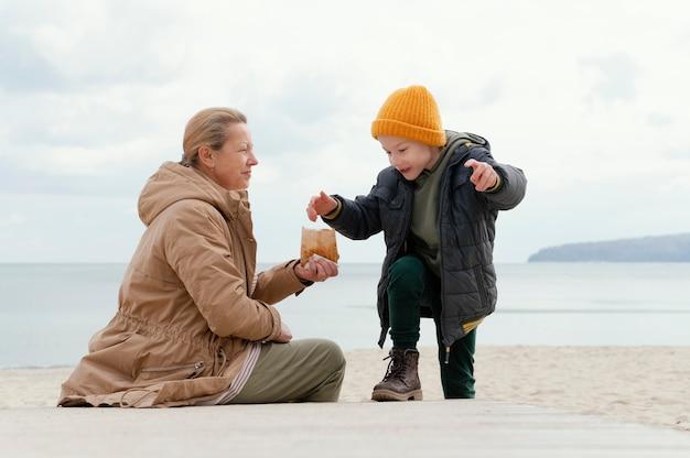 Mulher e criança na praia, tiro completo