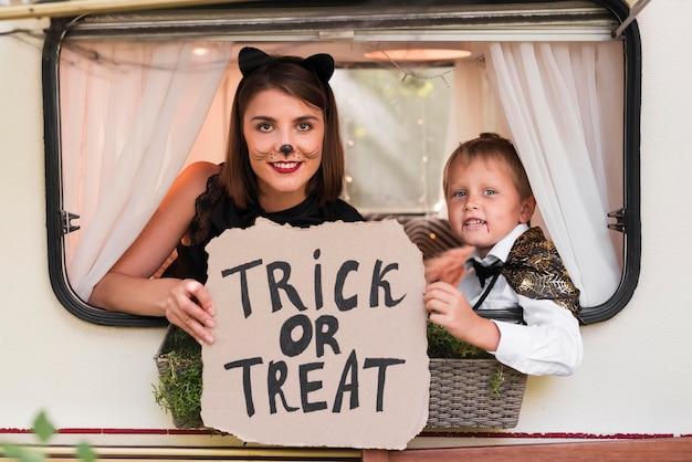 Mulher e criança posando com sinal de halloween