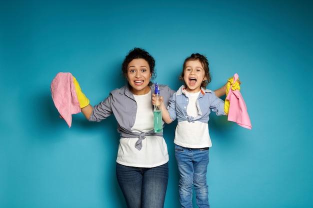 Mulher e criança posando em uma superfície azul com produtos de limpeza nas mãos