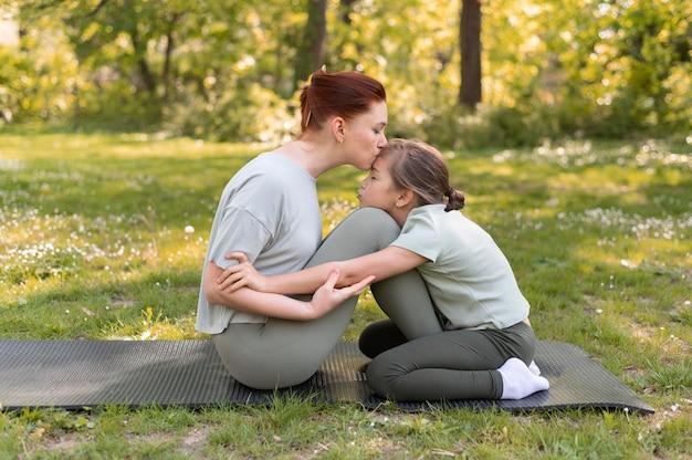 Mulher e criança sentadas juntas em cena completa