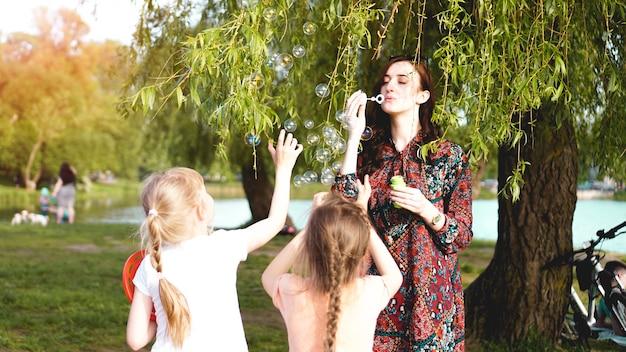 Mulher e crianças brincam com balões de sabão. retrato romântico de jovem com balões de sabão. sunny valley em um dia de verão