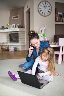 Mulher, e, dela, filha, sentar-se tapete, com, eletrônico, dispositivos