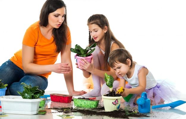 Mulher e duas meninas plantam flores em vasos
