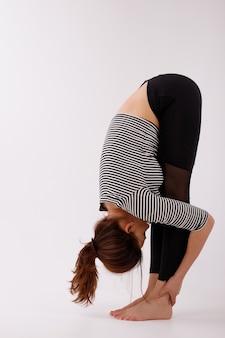 Mulher é esticada e entra para esportes em um fundo branco em roupas pretas. yoga e meditação