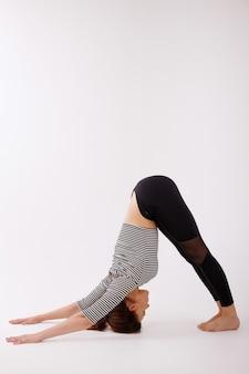 Mulher é esticada para esportes em um fundo branco em roupas pretas. yoga e meditação