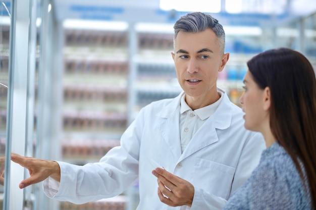 Mulher e farmacêutico atencioso perto de prateleiras com remédios