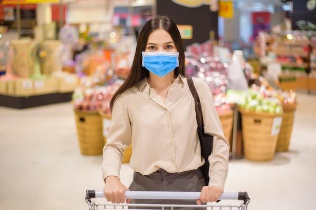 Mulher é fazer compras no supermercado com máscara facial