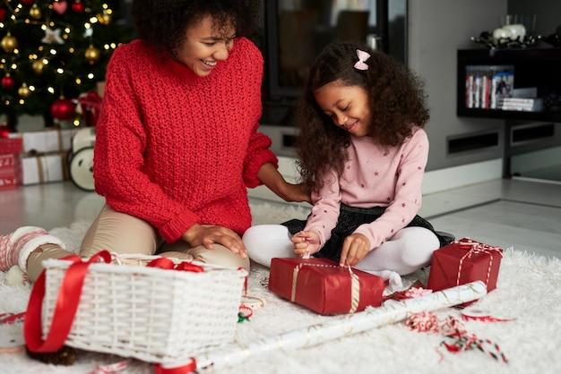 Mulher e filha embalando presentes de natal