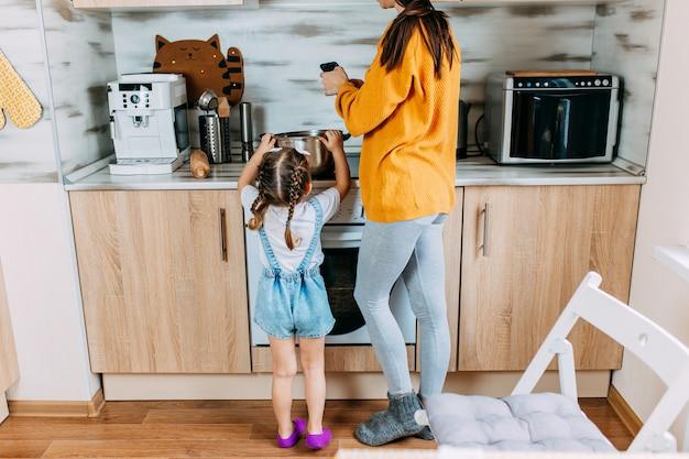 Mulher e filha estão cozinhando juntos