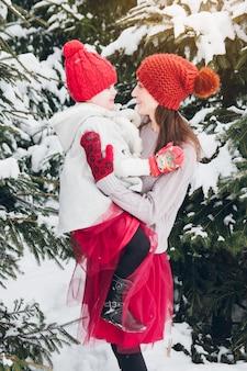 Mulher e filha se divertir na floresta de inverno