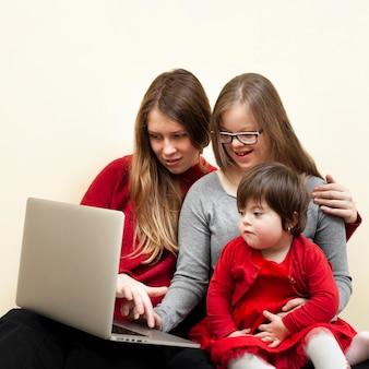 Mulher e filhos com síndrome de down olhando para laptop