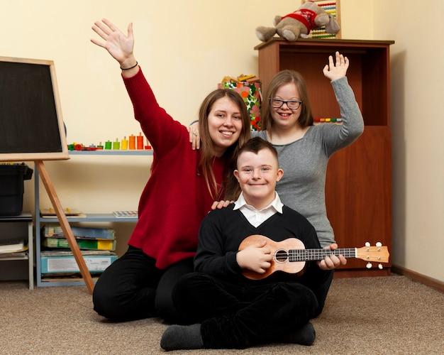 Mulher e filhos com síndrome de down sorriem e acenam