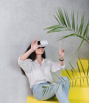 Mulher e fone de ouvido de realidade virtual e plantas