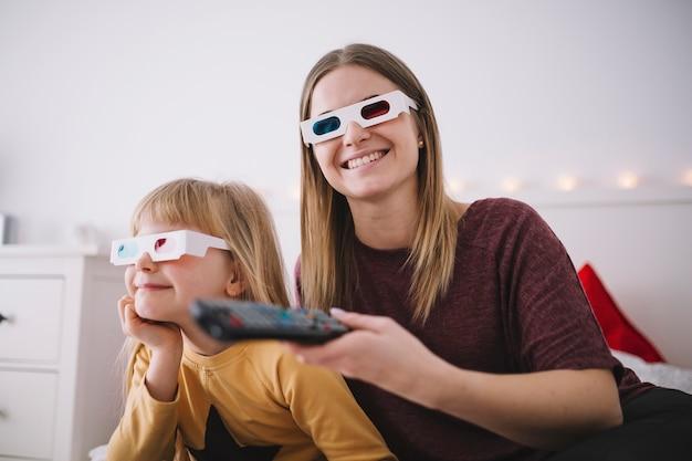 Mulher e garota alegre assistindo tv