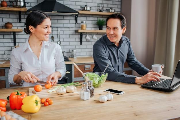 Mulher e homem adulto sentam à mesa na cozinha.