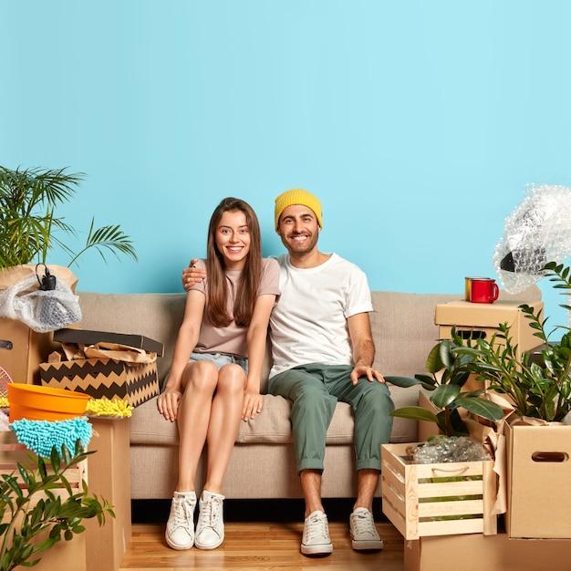 Mulher e homem alegres posam no sofá, se abraçam e se divertem juntos, mudam-se para o novo apartamento