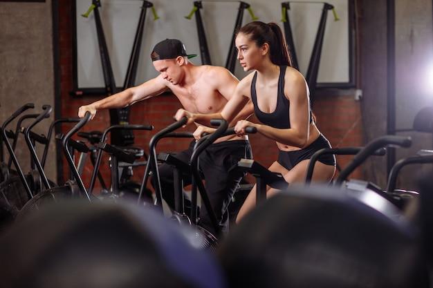 Mulher e homem, andar de bicicleta no ginásio, exercitar as pernas fazendo exercício cardio cardio bicicletas