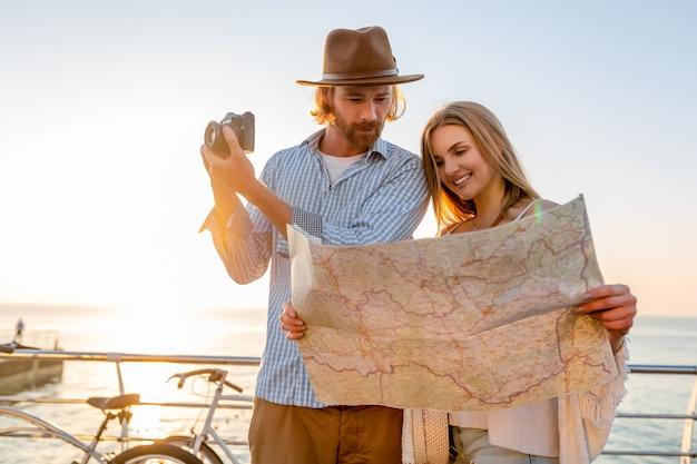 Mulher e homem apaixonado viajando de bicicleta no pôr do sol no mar