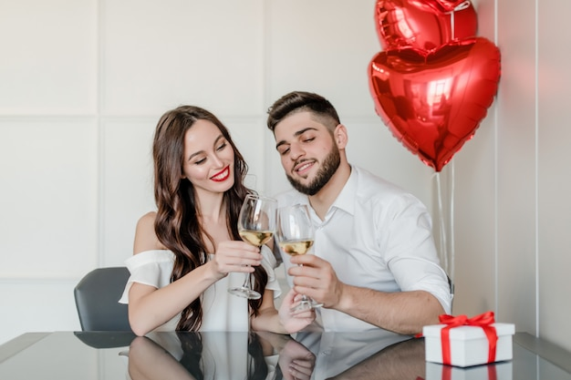 Mulher e homem bonito feliz bebem vinho branco em casa com presente na caixa de presente e balões em forma de coração vermelho em casa