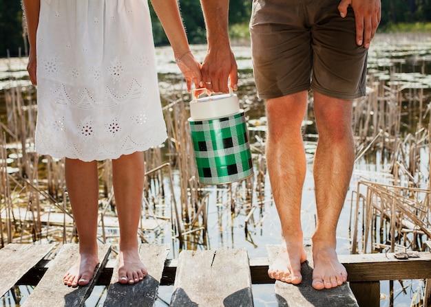 Mulher e homem com os pés descalços, segurando um tanque de água