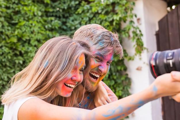Mulher e homem com rostos pintados tirando uma selfie sobre o arbusto