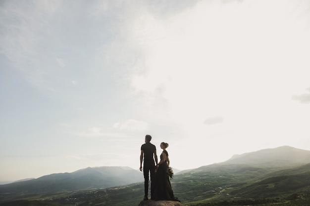 Mulher e homem com roupas pretas ao ar livre. vestido de noiva preto.