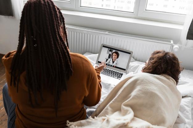 Mulher e homem conversando com um médico por videochamada