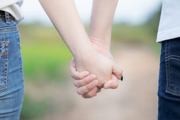 Mulher e homem de mãos dadas, casal feliz ama ao ar livre.
