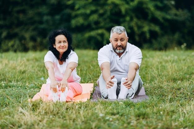 Mulher e homem de meia idade tomando exercício juntos siiting no tapete de ioga. esporte