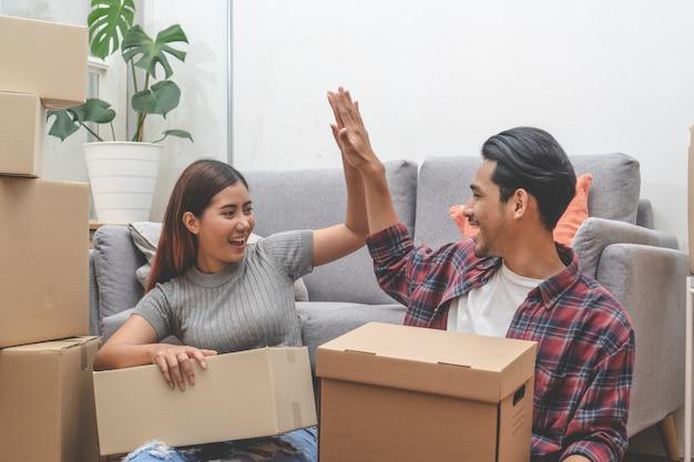 Mulher e homem descompactar caixas bagunçadas depois de se mudar para casa nova juntos.
