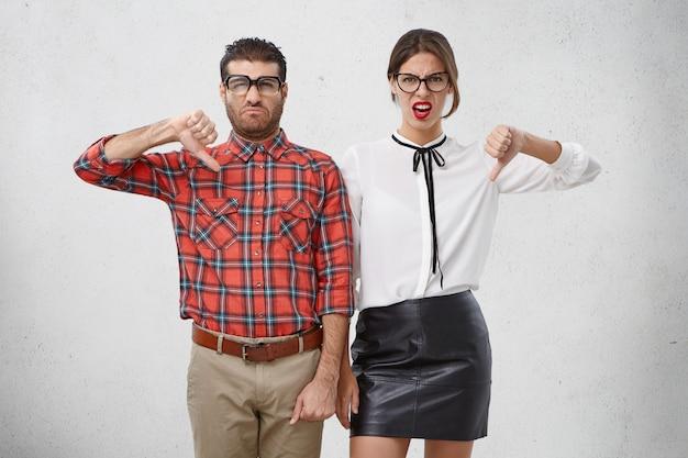 Mulher e homem descontentes mantêm os polegares abaixados, desaprovam algo, rostos carrancudos