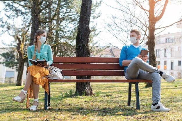 Mulher e homem em distanciamento social, sentado no banco
