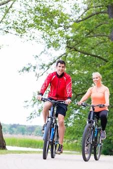 Mulher e homem em mountain bike na floresta