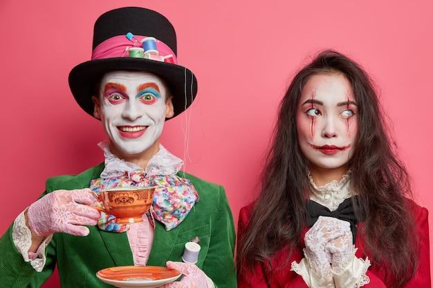 Mulher e homem em trajes de halloween e maquiagem profissional posam no interior contra uma parede rosa. chapeleiro maluco do país das maravilhas bebe chá