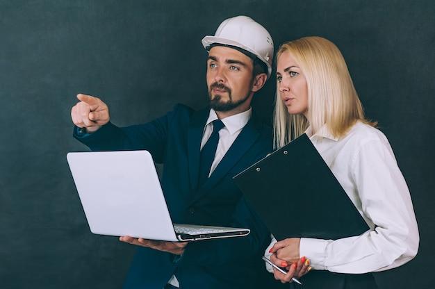 Mulher e homem em um capacete de construção com um laptop
